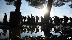 The sun rises as refugees and migrants walk to pass from the northern Greek village of Idomeni to southern Macedonia, Sept. 11, 2015.