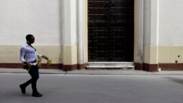 FILE - A woman walks past closed doors at the Church of Our Virgin of Charity in Havana March 14, 2012.