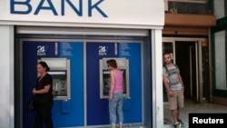希臘人8月12日在雅典一家銀行外使用提款機。