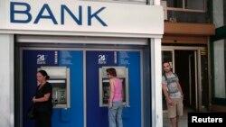 希腊人8月12日在雅典一家银行外使用提款机。