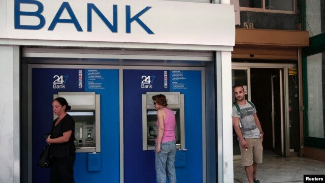 People make transactions at ATM machines outside a bank branch in Athens, Aug. 12, 2013.