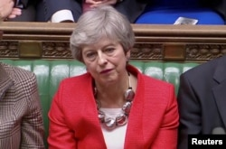 FILE - British Prime Minister Theresa May reacts after tellers announced the results of the vote Brexit deal in Parliament in London, Britain, March 12, 2019, in this screen grab taken from video.