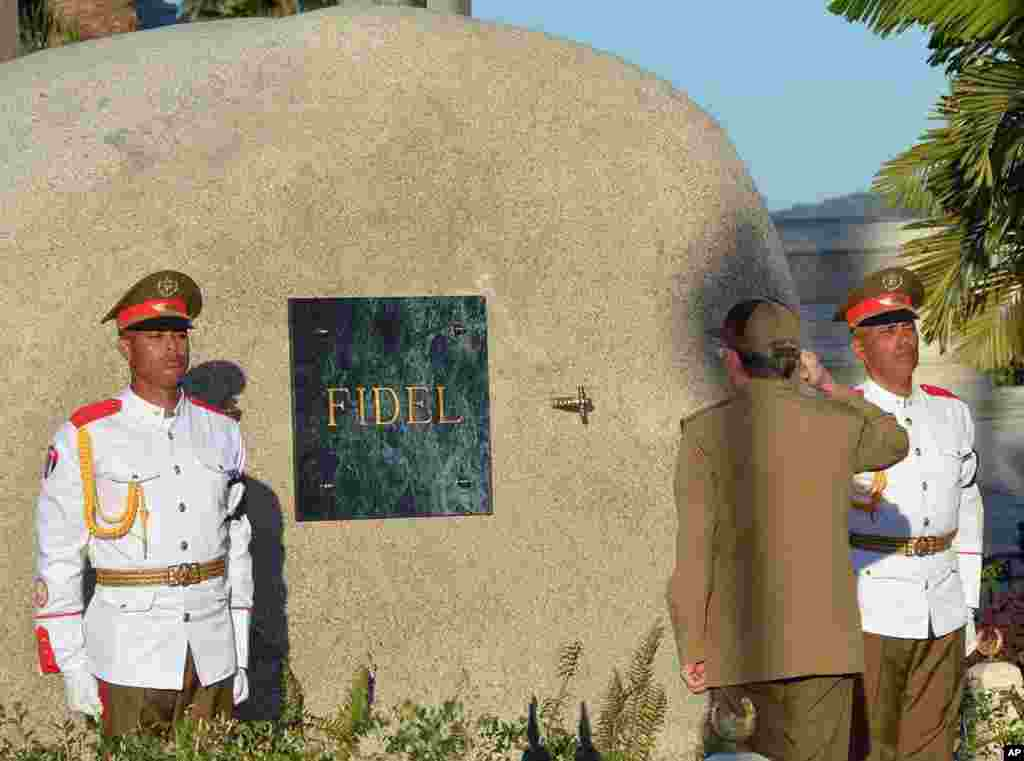 "Cuba's President Raul Castro salutes at the tomb of his older brother Fidel Castro, a simple, grey, round stone about 15 feet high, at the Santa Ifigenia cemetery in Santiago. Raul Castro placed the ashes in a niche in the tomb that was then covered by a plaque bearing the single name,""Fidel."""