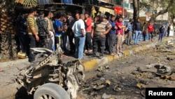 2013年2月17日巴格达卡拉达区的居民在检查被汽车炸弹袭击的一个地点