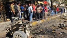 Residents are seen inspecting the site of a car bomb attack in the Karrada district in Baghdad February 17, 2013.