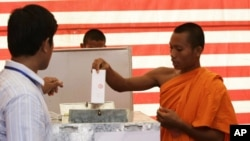 Cambodian Buddhist monk, right, casts his ballot in local elections at Wat Than pagoda's polling station in Phnom Penh, Sunday, June 3, 2012.