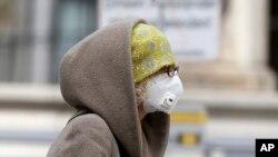 Seorang perempuan meggunan masker di Wina, Austria, 30 Maret 2020. (Foto: AP)