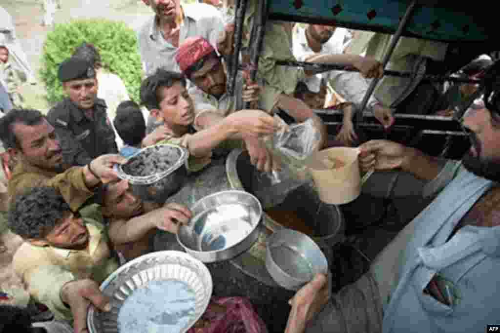 Pakistani men and boys gather to receive food at a camp for the displaced set up inside a college on the outskirts of Nowshera on August 2, 2010. Fears were growing Monday for up to 2.5 million people affected by Pakistan's worst floods in 80 years amid o