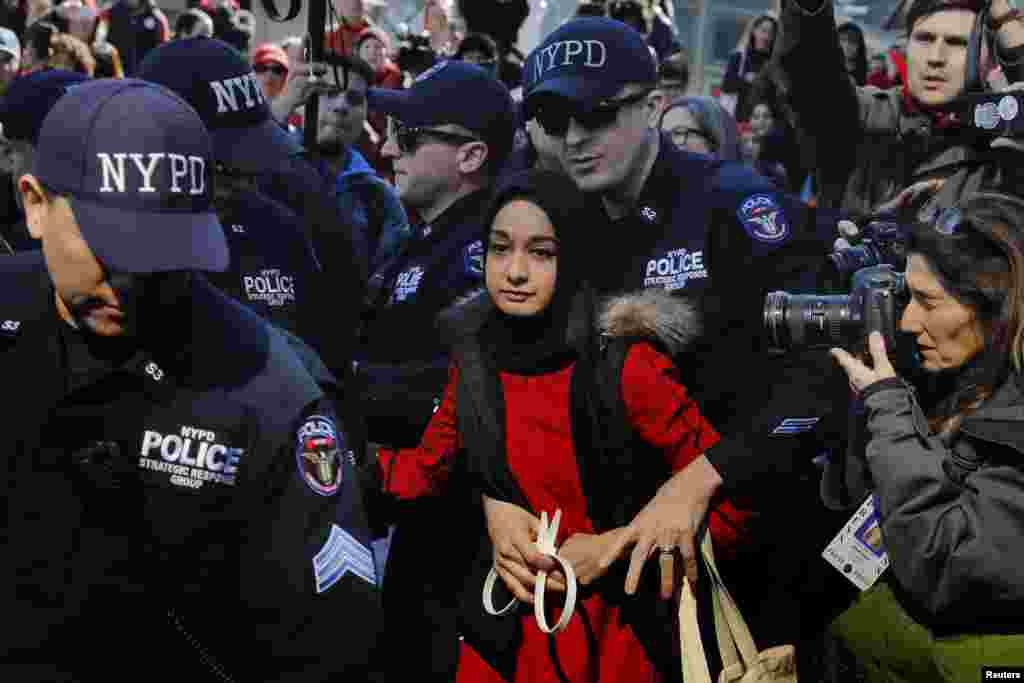 New York Police Department officers arrest a woman who is taking part in a 'Day Without a Woman' march on International Women's Day in New York, March 8, 2017.