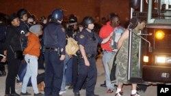 Người biểu tình bị bắt được đưa lên xe cảnh sát ở Cleveland, Ohio.