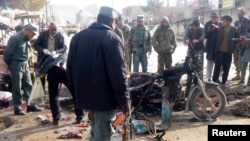An Afghan police officer stands at the site of a suicide blast in Faryab, northern Afghanistan, March 18, 2014.