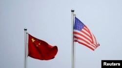 2021 年4 月14 日,美中兩國國旗在中國上海的一家公司大樓外飄揚。(路透社資料照片)