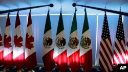 FILE - National flags representing Canada, Mexico, and the U.S. are lit by stage lights at the North American Free Trade Agreement, NAFTA, renegotiations, in Mexico City, Sept. 5, 2017.