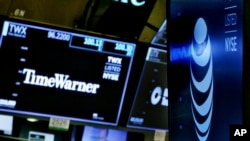 FILE - The logos for Time Warner and AT&T appear above alternate trading posts on the floor of the New York Stock Exchange.