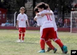 "Candelaria Cabrera watches her soccer teammates celebrate a goal against Alumni in Chabaz, Argentina. ""Cande,"" as she is known by friends and family, is the only girl playing in a children's soccer league in the southern part of Argentina's Santa Fe province, birthplace of stars including Lionel Messi, Gabriel Batistuta and Jorge Valdano."