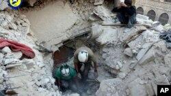 """叙利亚民防队提供的这张照片显示,在阿勒颇的布斯坦艾巴夏区遭到空袭之后,""""白盔""""志愿救援组织的民防人员在废墟中挖掘尸体,并寻找生还者。"""