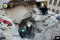 FILE - This photo shows Syrian Civil Defense White Helmets digging in the rubble to remove bodies and look for survivors, after airstrikes hit the Bustan al-Basha neighborhood in Aleppo.