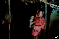 In this Aug. 27, 2018, photo, Rohingya refugee woman Minara Begum, mother of Rahima Akter, holds her youngest daughter Arohi Zannat inside the family hut in Kutupalong refugee camp, Bangladesh.