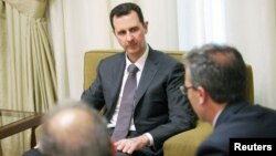 Syria's President Bashar al-Assad (C) is seen during an interview with the al-Thawra newspaper in Damascus in this handout photograph distributed by Syria's national news agency SANA, July 3, 2013