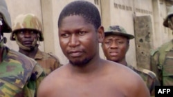 FILE - Handout photo obtained on August 5, 2009 shows Mohammed Yusuf surrounded by soldiers at Giwa Barracks in Maiduguri, northeastern Nigeria, on July 30, 2009 shortly after his capture by Nigerian troops.