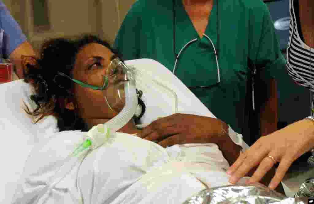 Mwanamke akipata msaada katika hospitali ya Palermo Civico baada ya kuokolewa katika kisiwa cha Lampedusa nchini Italy.