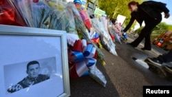 A picture of victim Drummer Lee Rigby, of the British Army's 2nd Battalion The Royal Regiment of Fusiliers is displayed with flowers left by mourners outside an army barracks near the scene of his killing in Woolwich, southeast London May 23, 2013.