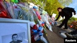 2013年5月23日在伦敦南部一处兵营附近英国士兵里格比被杀害的现场附近在里格比的照片旁边人们放置鲜花,对里格比的死亡表示哀悼。