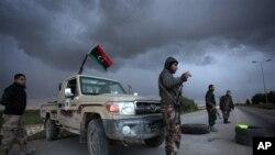 Libyan security forces stand guard at a checkpoint on the highway leading to downtown Benghazi, Libya, Feb. 15, 2013. Libyans are preparing to mark the second anniversary of the uprising that ousted Moammar Gadhafi.