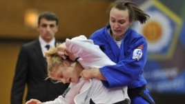Kayla Harrison of US, in white, fights with Vera Moskalyuk of Russia during the women's under 78 kg category final match at the World Cup Judo tournament in Budapest, Hungary, February 12, 2012.