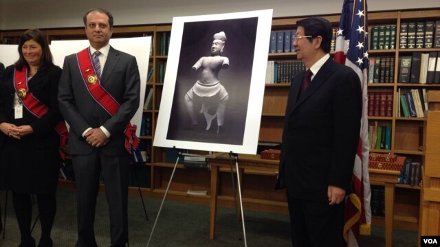 U.S. Attorney Preet Bharara, left, and Cambodian Cabinet Minister Sok An, at a ceremony marking the repatriation of an ancient Khmer statue, which is shown in a picture. (R. Poch/VOA)
