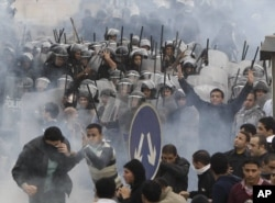 FILE - Egyptian anti-government activists clash with riot police in Cairo, Egypt, Jan. 28, 2011.