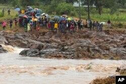 Schoolchildren are stranded across a collapsed bridge in Chimanimani, southeast of Harare, Zimbabwe, March 18, 2019.