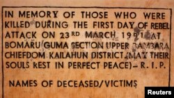 FILE - A sign commemorating the start of the civil war is displayed April 22, 2012, at a memorial site where the conflict began, in the village of Bomaru, eastern Sierra Leone. Sierra Leone's 11-year conflict from 1991-2002 left over 50,000 dead and became a byword for gratuitous violence, especially the amputation of limbs.