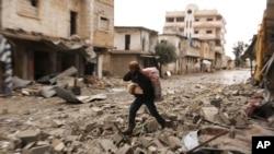 Un homme transporte ses effets personnels dans une rue détruite dans la ville de Sarmin, dans la province d'Idbleb, en Syrie, le 7 février 2020. (Photo AP / Ghaith Alsayed)