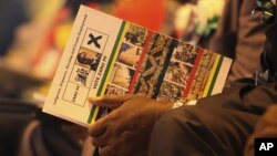 A supporter of Zimbabwean President Robert Mugabe holds a campaign card at Zanu-PF 13th annual conference in Gweru in December 2012.