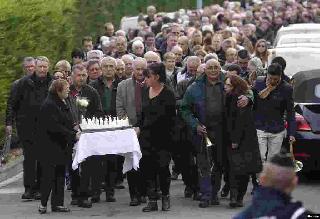 Warga memberi penghormatan dua hari setelah kecelakaan bus di Puisseguin, Perancis baratdaya, yang menewaskan 41 orang. Bus itu, yang mengangkut pensiunan untuk karyawisata, bertabrakan dengan sebuah truk dan lalu terbakar.