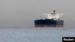 """FILE - Malta-flagged Iranian crude oil supertanker """"Delvar"""" is seen anchored off Singapore, March 1, 2012."""