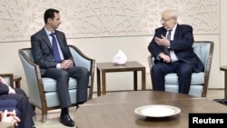 In a photo released by Syria's national news agency, SANA, Syria's President Bashar al-Assad, left, talks to Jean-Pierre Vial, leader of a delegation of French lawmakers, in Damascus, Feb. 25, 2015.