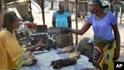 FILE - A street trader sells dried fish and smoked monkey meat at the port of Maluku in Kinshasa, Congo, May 29, 2018.