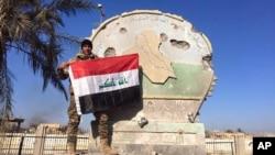 Một binh sĩ Iraq giương cờ trên công ốc chính phủ ở Ramadi, Iraq, ngày 28/12/2015.