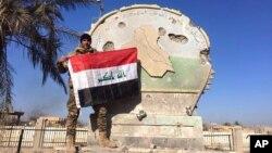 Иракский солдат c национальным флагом на вершине правительственного комплекса в центре Рамади. Ирак, 28 декабря 2015.