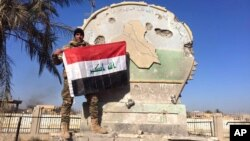 An Iraqi soldier holds a national flag atop the government complex in central Ramadi, Iraq, Dec. 28, 2015.
