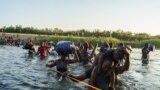 Мигранты из Гаити переходят вброд реку Рио-Гранде на границе между Мексикой и США. 20 сентября 2021г.