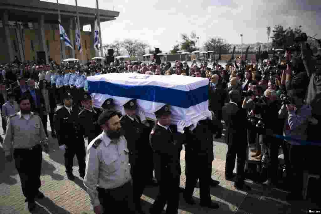 Members of the Knesset guard carry the flag draped coffin of former Prime Minister Ariel Sharon as his family members walk behind during a memorial ceremony at Israel's parliament in Jerusalem, Jan. 13, 2014.