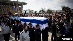 ທະຫານຍາມຕຶກສະພາ Knesset ຫາມຫີບສົບຂອງ ມື້ລາງນາຍົກລັດຖະມົນຕີ Ariel Sharon ທີ່ປົກຄຸມດ້ວຍທຸງຊາດ ໂດຍມີຄອບຄົວຂອງທ່ານ ຍ່າງຢູ່ທາງຫລັງ ໃນລະຫວ່າງພິທີໄວ້ອາໄລ, ວັນທີ 13 ມັງກອນ 2014.