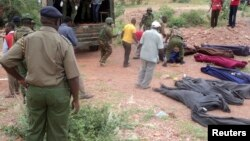 Des militaires kenyans et volontaires de la Croix-Rouge transportent des corps dans une carrière dans le village de Korome, à proximité de Madera le 2 décembre 2014.