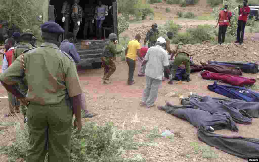 Kenyan military personnel and Red Cross volunteers carry bodies of people killed at a quarry in a village in Korome, outside the border town of Mandera, Dec. 2, 2014.