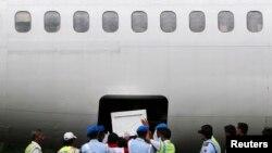 Tentara Indonesia dan personel penyelamatan memasukkan peti jenazah korban AirAsia bernomor penerbangan QZ8501 ke dalam kargo pesawat Trigana di pangkalan udara Iskandar, Pangkalan Bun (27/1). (Reuters/Beawiharta)