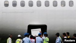 Indonesia soldiers and rescue personnel put a coffin of a passenger of AirAsia Flight QZ8501 into the cargo compartment of a Trigana airplane, file photo.