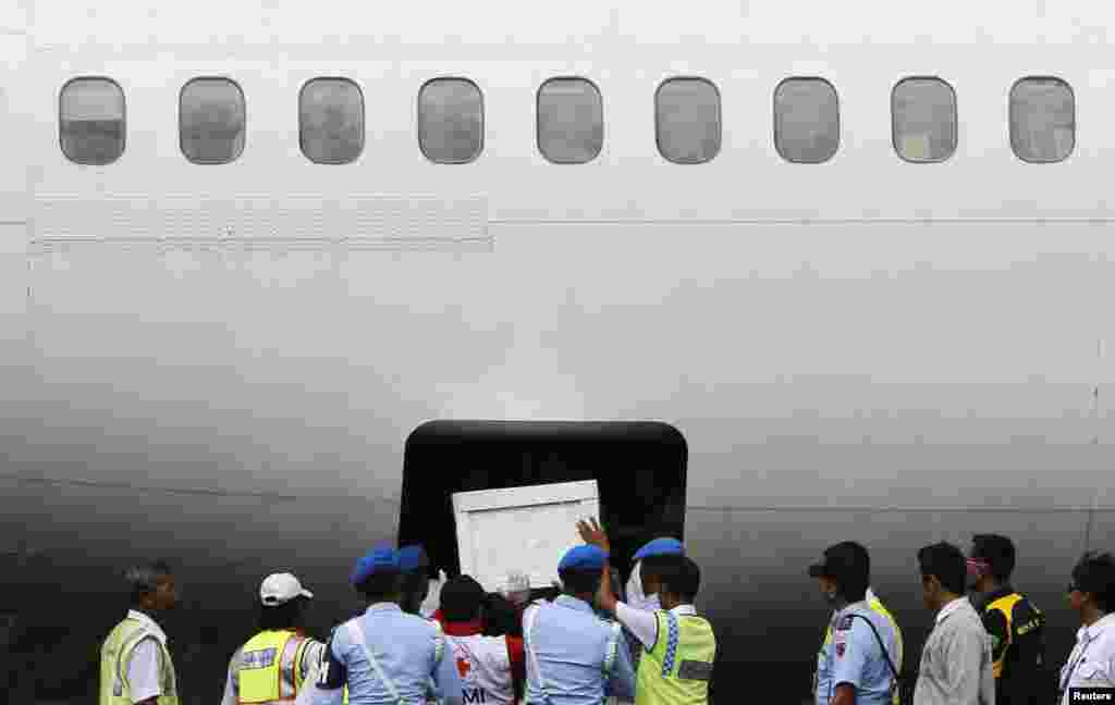 Indonesian soldiers and rescue personnel put a coffin of a passenger of AirAsia Flight QZ8501 into the cargo compartment of a Trigana airplane at Iskandar airbase in Pangkalan Bun.